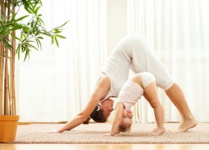 Mother and daughter doing yoga exercise home. Mother and baby g